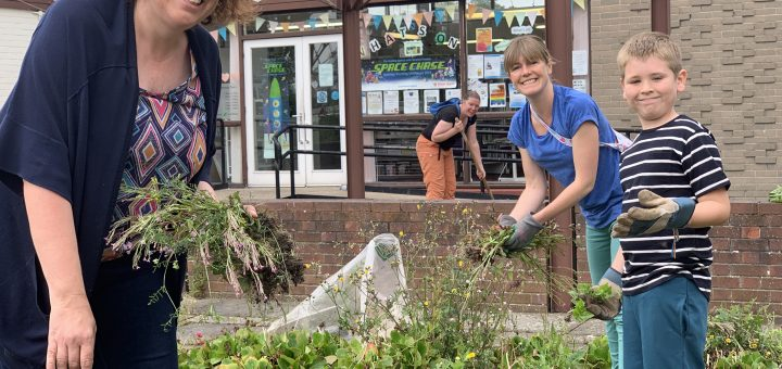 Four smiling volunteers planting beds outside the Newtongrange Library