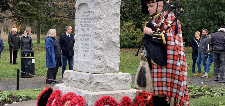 Piper in full regalia stands by the stone war memorial at Newtongrange